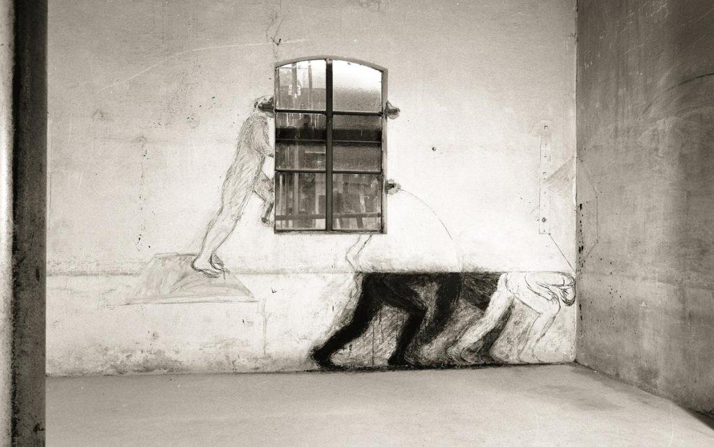 Zeichnung mit Kreide und Kohle auf Wand unter Einbeziehung einer vorhandenen Linie auf der Wand, im Raumeck Papiercollage und Schnur, am Fenster Collage und Zeichnung mit vorgefundenem Mauerloch