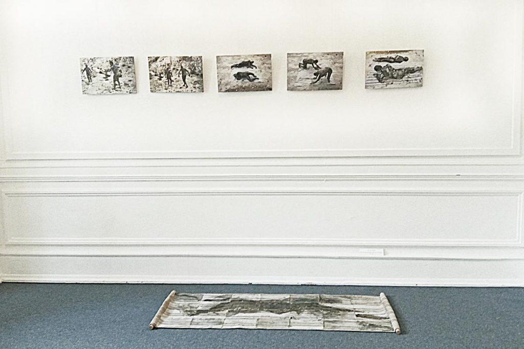 """""""Auf der Suche nach einem Lager für den Nachlass"""", fünf Fotos an der Wand, je 26 x 41 cm (1991) und Stoff (Betttuch) auf Boden, 65 x 154 cm, Fangoerde, Leim, Kreide, zwei Holzstäbe (1991 und 2018)"""
