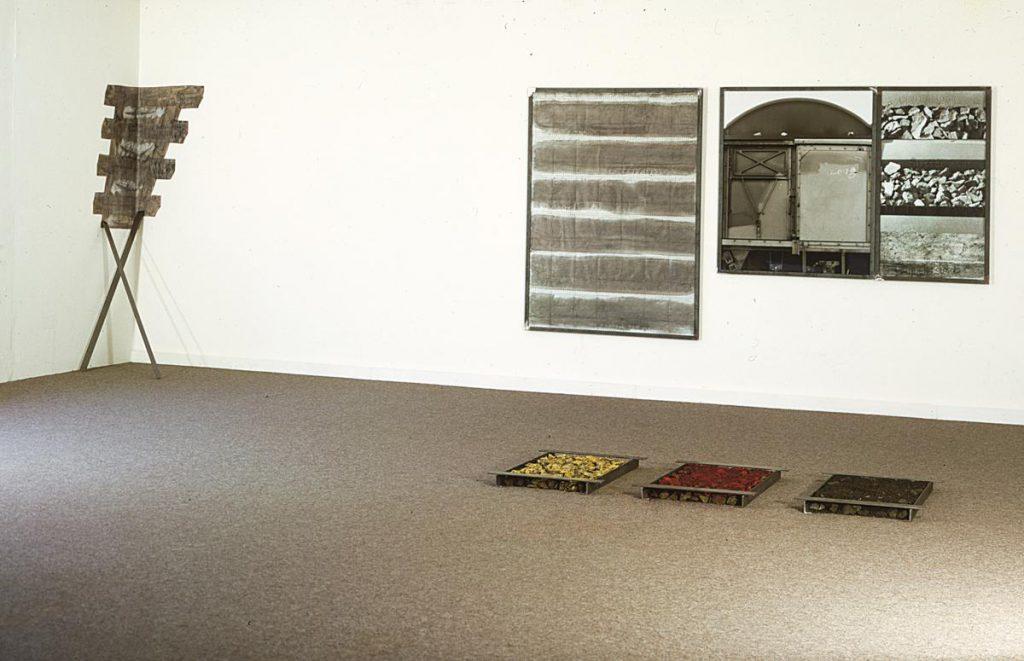 """""""Ringbahn"""", an der Wand: Fotomontage 2-teilig, Frottagen der Gleise, bemaltes Papier (Gleise) und 2 Metallschienen im Eck, auf dem Boden Steine von der Ringbahn, Winkeleisen und Metallschienen, Kohlegris (schwarz), Rost (rot) und fränkischer Sand (gelb), 1991"""